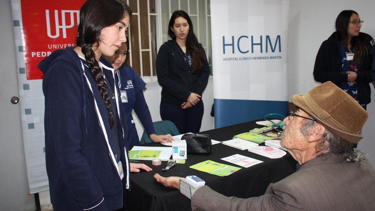 Imagen de adulto mayor tomándose la presión arterial en puesto informativo en el marco de la conmemoración de la Semana del Riñón en el Hospital de Chillán.